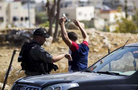 Un policier israélien contrôle un Palestinien à un barrage dans une zone de la Cisjordanie, le 14 octobre.