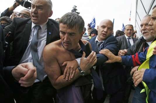Le responsable des ressources humaines Xavier Broseta, torse nu, est évacué par des agents de sécurité lors du conseil d'entreprise d'Air France à Roissy le 5 octobre 2015.