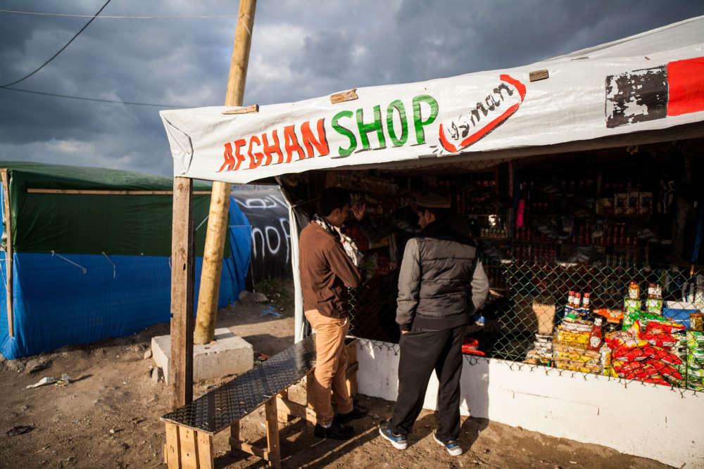 """Officiellement ouvert au printemps pour libérer le centre-ville de ses migrants et les regrouper, la """"jungle"""" a pris l'aspect  d'un immense bidonville, structurée par une économie de survie. Les magasins affichent souvent l'origine du propriétaire."""