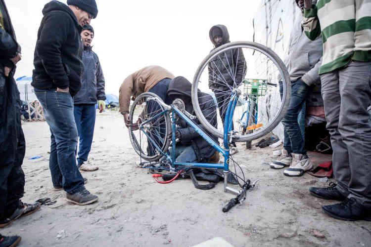 Dans la jungle, un des migrants propose ses services pour réparer les vélos des autres occupants du camp. Comme pour se donner l'impression de reprendre la main, les CRS ont réinvesti le lieu. Lundi 12 octobre, avant le déjeuner, ils ont patrouillé par groupe de quatre ou cinq et tassé un peu plus le sable de la dune de leurs bottes de sécurité.