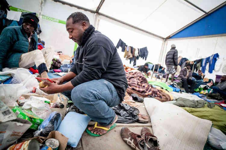 Mohajir épluche quelques pommes de terre pour le repas du soir. Dans la grande tente des Soudanais, l'accueil se veut chaleureux.
