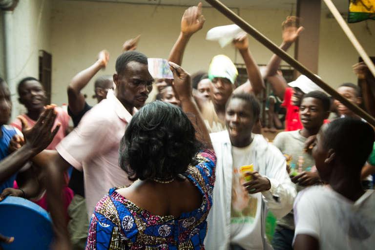 Des jeunes venus soutenir le candidat Konan Kouadio Simeo dans la cour du chef de village d'Abadjin Kouté. Pour récompenser leur mobilisation, l'épouse du candidat leur remet un billet de 10 000 francs CFA.