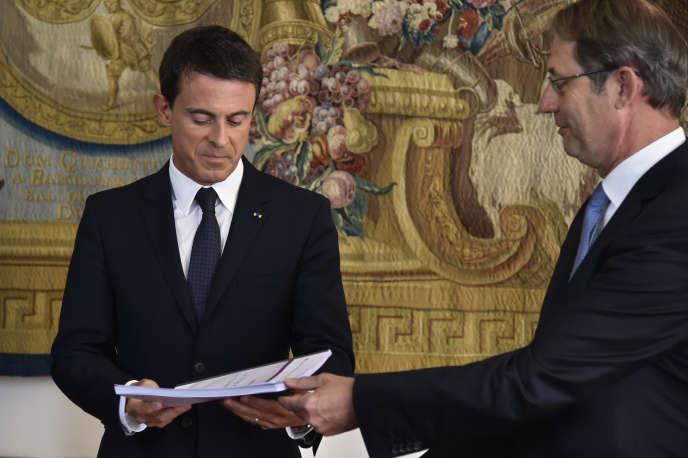 Manuel Valls reçoit le texte de la réforme du droit du travail des mains de  Jean-Denis Combrexelle le 9 septembre 2015 à Paris.