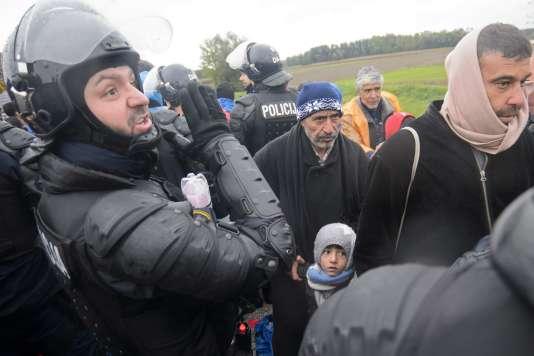 Un policier slovène fait passer des migrants venus de Croatie, à Trnovec le 19 octobre.