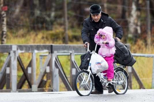 Un homme pousse une enfant sur un vélo aux pneus crevés pour traverser la frontière russo-norvégienne que la Russie interdit de passer à pied.