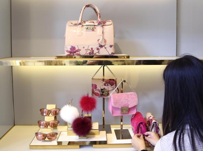 Une vendeuse arrange une vitrine du magasin Furla, à Milan.