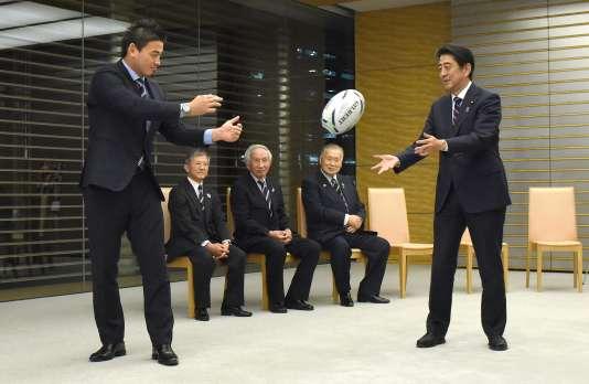 Le premier ministre japonais, Shinzo Abe (à droite), reçoit une passe de l'arrière du XV nippon Ayumuru Goromaru, le 21 octobre à Tokyo.
