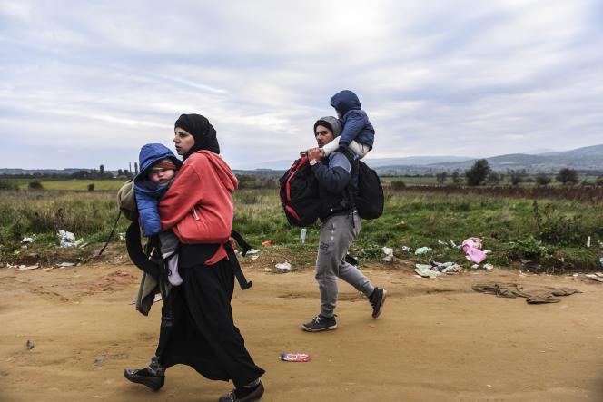 Des migrants portent leurs enfants sur une route après être entrés en Serbie depuis la Macédoine, le 21 octobre 2015.