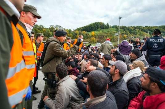 Migrants et réfugiés attendent de pouvoir monter dans des bus après avoir passé la frontière entre la Slovénie et l'Autriche à Spielfeld jeudi 22 octobre.