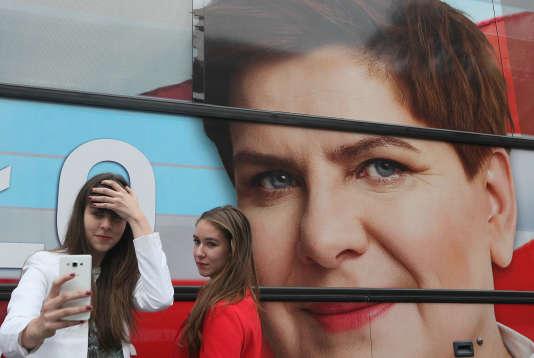 A Varsovie, un selfie devant une affiche pour Beata Szydlo, la chef de campagne du parti conservateur, le mieux placé dans les sondages pour les législatives polonaises.(AP Photo/Czarek Sokolowski)