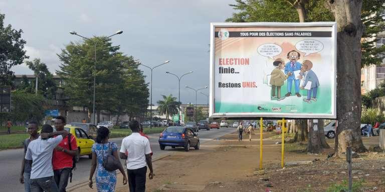 Des Ivoiriens passant sous affiche invitant au calme après l'élection du 25 octobre 2015.