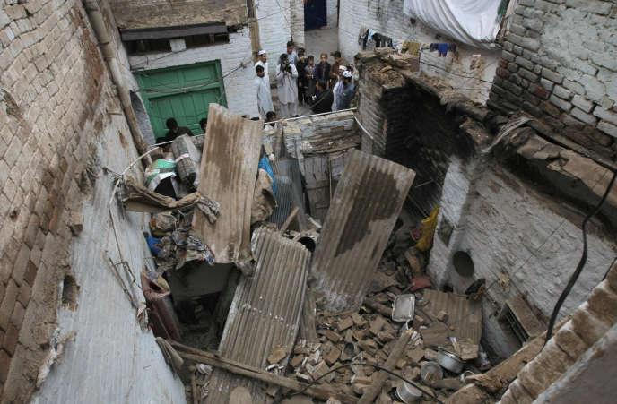 Des habitants de Peshawar, au Pakistan, près des décombres d'un immeuble qui s'est effondré après le tremblement de terre qui a frappé l'Asie du sud le 26 octobre.