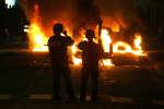 Des policiers sont postés à proximité de véhicules incendiés, le 28 octobre 2005 à Clichy-sous-Bois.