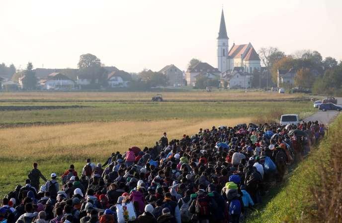 Des migrants escortés par des policiers et des soldats slovènes, près du village de  Rigonce, lundi 26 octobre.