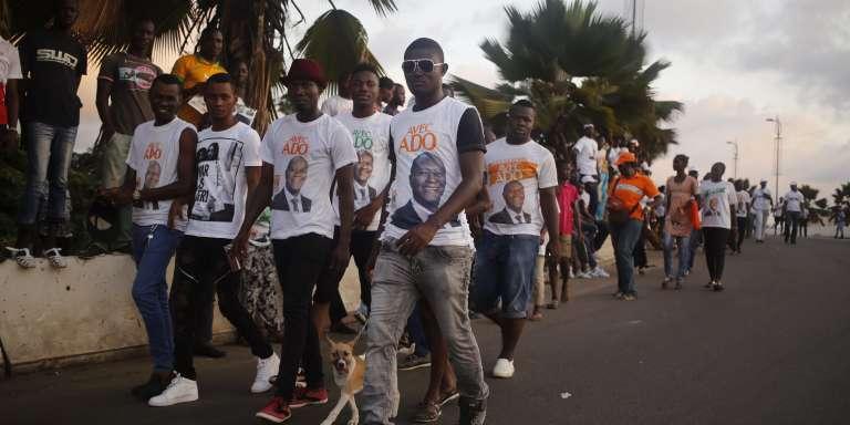 Des partisans d'Alassane Ouattara défilent avec des tee-shirts à son effigie, à Abidjan, le 23octobre.