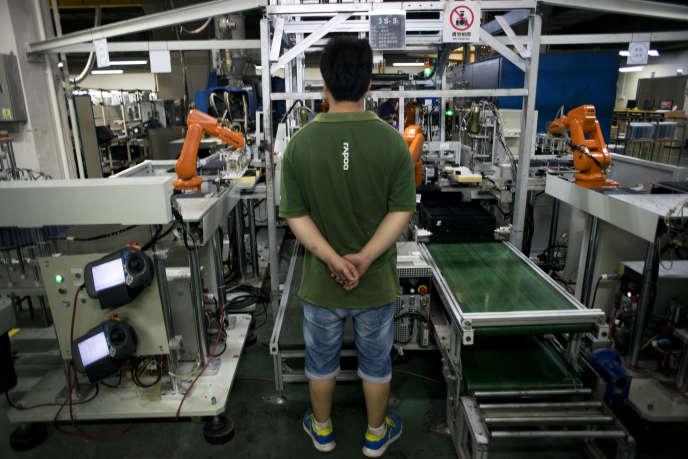 Production robotisée de claviers d'ordinateur. Un opérateur surveille le bon fonctionnement des machines.    Usine RAPOO, Shenzhen, Chine. Shenzhen Rapoo Technology Co.