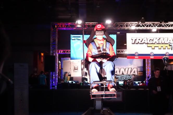 Un «cosplayeur» Mario teste un casque de réalité virtuelle sur un siège dynamique à la Paris Games Week.