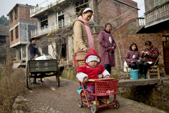 A young mother pushes her son on a walker through a rural village in Shangrao. The villages near the city of Shangrao are known for openly defying China's one child policy as most families have more than one child.