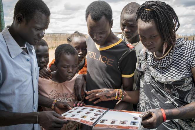 Des déplacées recherchent des membres perdus de leur famille  dans un registre établi le Comité international de la Croix-Rouge.
