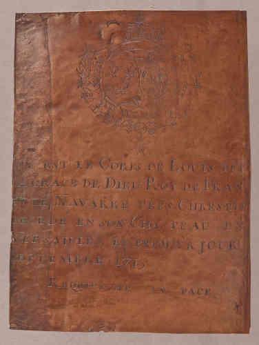 La plaque de cuivre, fixée sur le cercueil de Louis XIV en 1715, a été arrachée, le 14 octobre 1793, lors de la profanation des sépultures royales. Elle fut transformée en casserole par un chaudronnier de Saint-Denis.