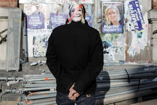 """Un membre des """"chicons en colère"""" devant un mur sur lequel sont collées des affiches du FN à Armentières le 31 octobre 2015."""
