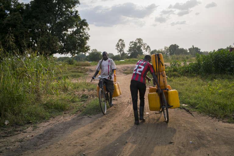 Des vendeurs d'eau ougandais remplissent des bidons en puisant dans le Nil Blanc.