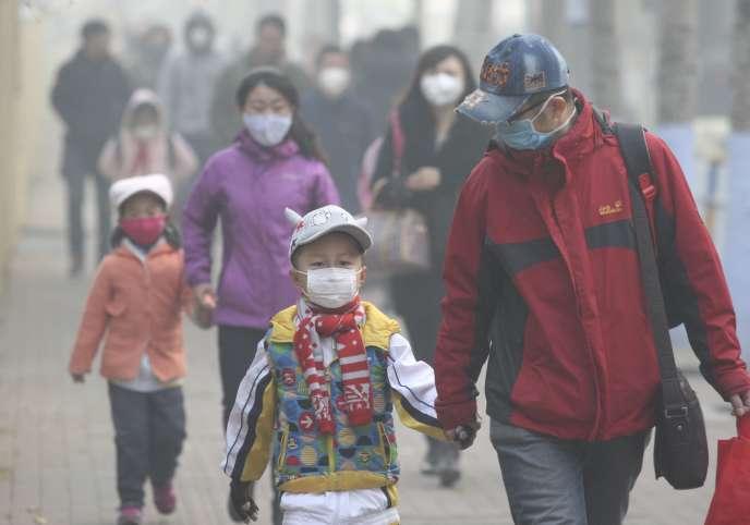 Des enfants et leurs parents portant des masques, dans une rue de Harbin, ville de la province de Heilongjiang en Chine, le 3 novembre 2015, un jour de pollution sévère.