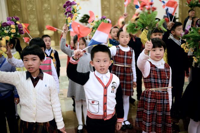 Des écoliers chinois agitent des drapeaux français dans la grande salle du Palais du peuple, à Pékin, le 2 novembre.