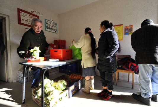 Un bénévole du Secours Catholique (G) distribue des colis de nourriture de la Banque Alimentaire, le 4 décembre 2009 à Saint-Eloy-les-Mines.