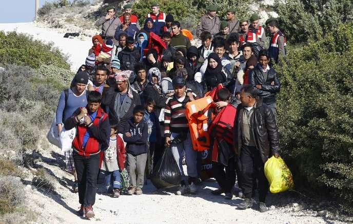 Sur une plage turque près de Cesme, des policiers empêchent un groupe de migrants de prendre la mer à bord de canots gonflables en direction de l'île grecque de Chios, le 5 novembre 2015.