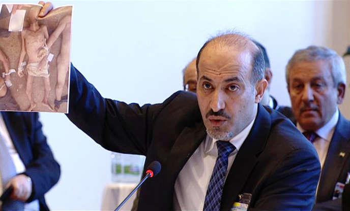 Ahmed Jarba, chef de la Coalition nationale syrienne, brandit, le 22 janvier 2014 à Montreux, une des photographies de victimes du régime syrien prises par « César ».