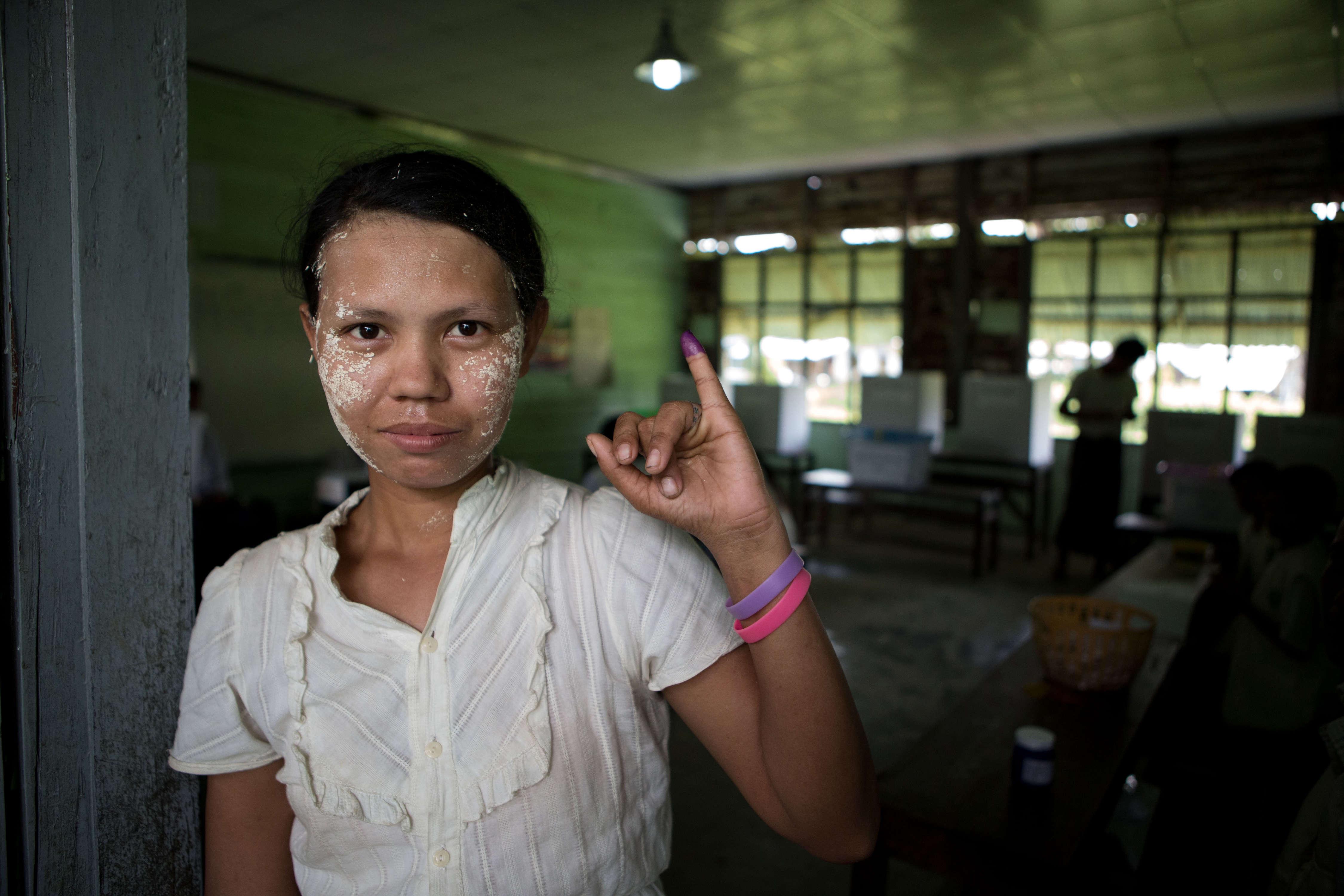 Les élections législatives du dimanche 8 novembre en Birmanie marquent le tournant démocratique pour le pays. Ici, une femme birmane présente son doigt marqué à l'encre pour attester qu'elle a voté, à Dala, en périphérie de Rangoun.