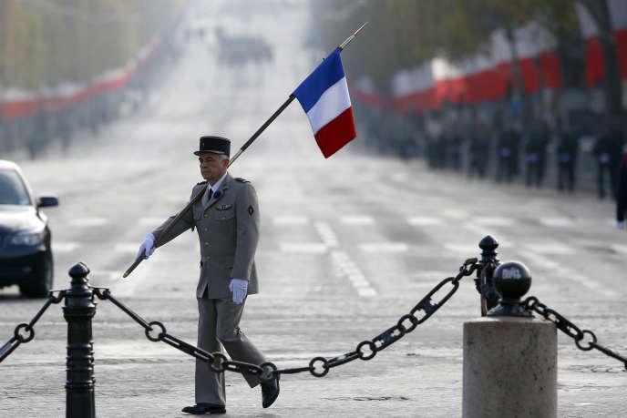 Un militaire portant un drapeau lors des cérémonies du 11-Novembre à l'arc de Triomphe, à Paris en 2015.
