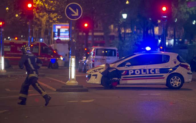 Un policier s'abrite derrière une voiture pour échapper aux tirs des terroristes entrés dans le Bataclan, le 13 novembre au soir.