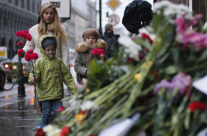 Une famille déposant des fleurs à l'ambassade de France à Saint-Pétersbourg (Russie).