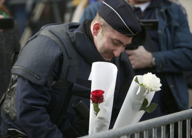 Un policier dispose des fleurs à proximité du Bataclan, le 14 novembre