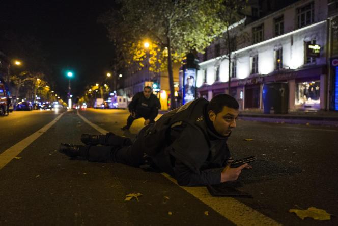 Des policiers se mettent à couvert tandis que des individus tirent dans leur direction, le 13 novembre  boulevard des Filles-du-Calvaire à Paris, à 500 mètres de la salle du Bataclan dans laquelle se déroule au même moment une attaque terroriste.