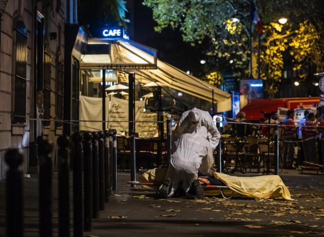 Des policiers inspectent le corps d'une victime de l'attaque du Bataclan, vendredi 13 novembre.