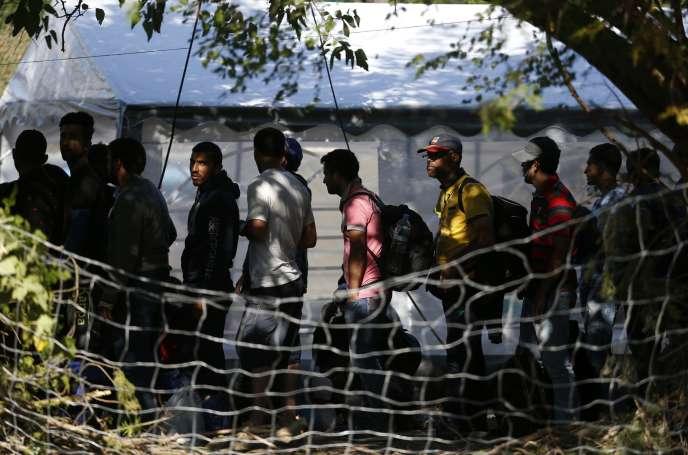Des migrants attendent à l'entrée d'un centre de réfugiés à Presovo en Serbie, en août.