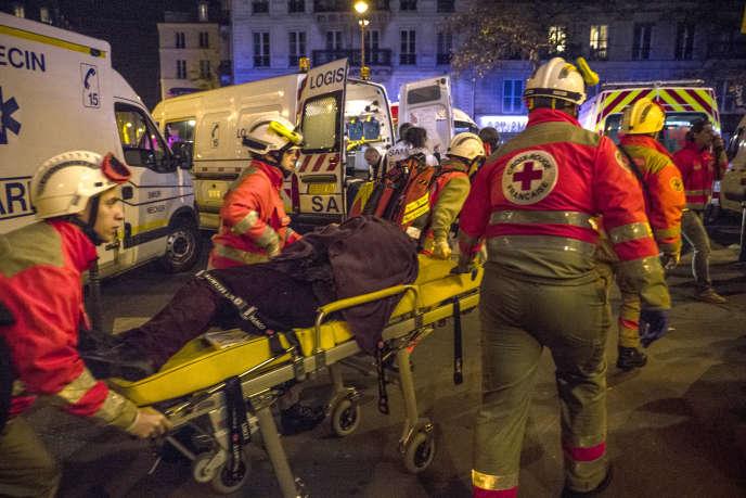 Des secouristes s'occupent des blessés, le 13 novembre 2015, boulevard des Filles du Calvaire, à Paris, à proximité de la salle du Bataclan dans laquelle se déroule au même moment une attaque terroriste.