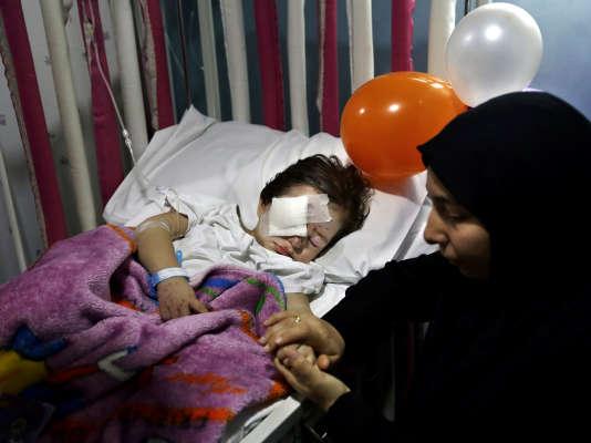 Adraa Taleb tient la main de son petit cousin, Haidar Mustafa, 3 ans, blessé lors du double attentat à la bombe, jeudi 12 novembre, dans le la banlieue sud de Beyrouth. Les parents de l'enfant figurent parmi les 44 victimes.