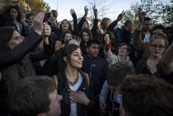 Des jeunes gens chantent, le 15 novembre 2015 sur la place de la République à Paris, en hommage aux victimes des attentats de Paris.