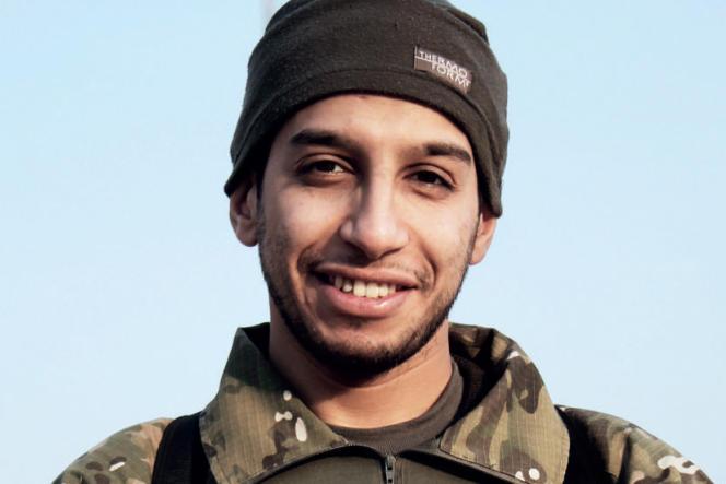 Cliché non daté d'Abdelhamid Abaaoud, devant le drapeau de l'Etat islamique et publié dans le numéro de février de la revue officielle djihadiste «Dabiq».