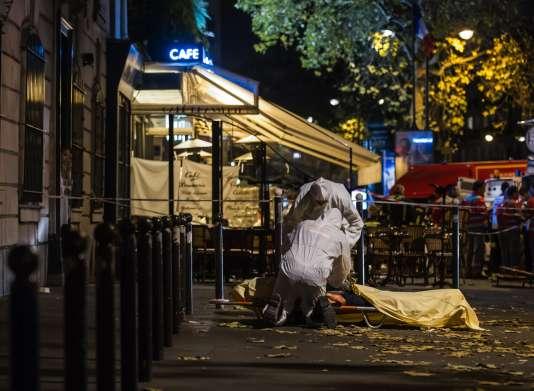 Des policiers de la police scientifique inspectent le corps d'une victime de l'attentat devant le Bataclan à Paris le 13 novembre 2015.