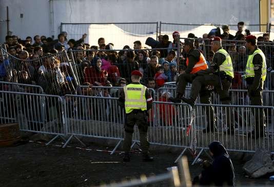 Des militaires autrichiens surveillent des migrants qui attentent de pouvoir pénétrer en Autriche, en novembre 2015.