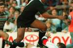 """(FILES) A file photo taken on June 18, 1995, shows New Zealand's wing Jonah Lomu as he tries to jump over England's fullback Mike Catt during the Rugby World Cup semi-final match between New Zealand and England in Cape Town. The All Blacks beat England 45-29.  Former England international Mike Catt said Jonah Lomu had """"put me on the map"""" for the """"wrong reasons"""" as he paid a fond tribute to the late New Zealand star. Lomu's sudden death at the age of 40 on November 18, 2015, shocked the international rugby union community and led many to recall his breakthrough performance at the 1995 World Cup in South Africa where he established himself as a global superstar of the sport.  AFP PHOTO / VINCENT AMALVY"""