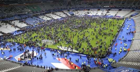 Des spectateurs attendent sur la pelouse du Stade de France après le match France-Allemagne, vendredi 13novembre.