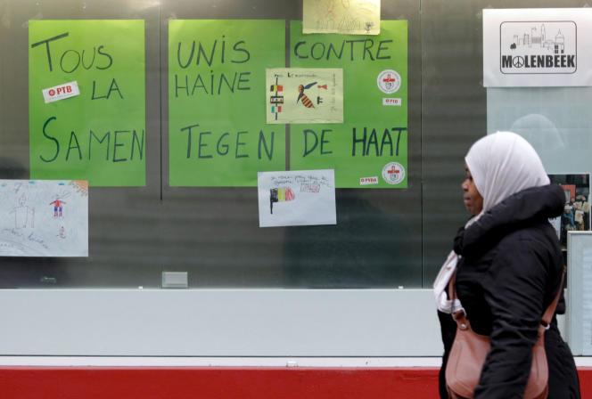 Une femme du quartier marche devant des pancartes