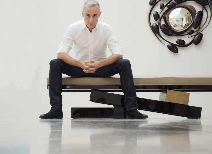 Hervé Van der Straeten est assis sur sa banquette Jet Lag. Derrière lui, le miroir Tumulte.