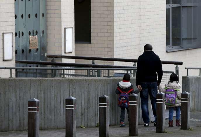 Un homme et ses deux enfants devant une école primaire fermée, à Bruxelles le 23 novembre 2015.